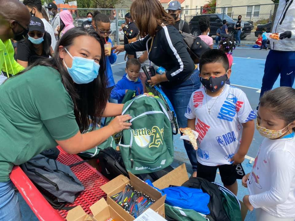 Councilmember Sheng Thao hands out backpacks to students on the first day of school