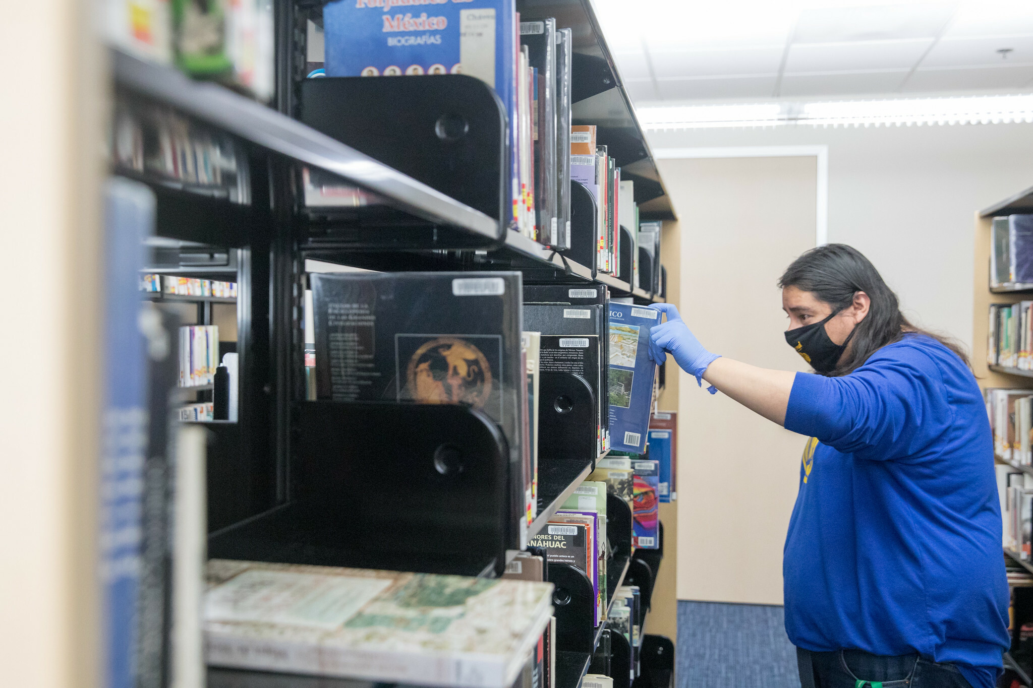A man in a blue shirt and a black mask browses the shelves at Chavez Branch.
