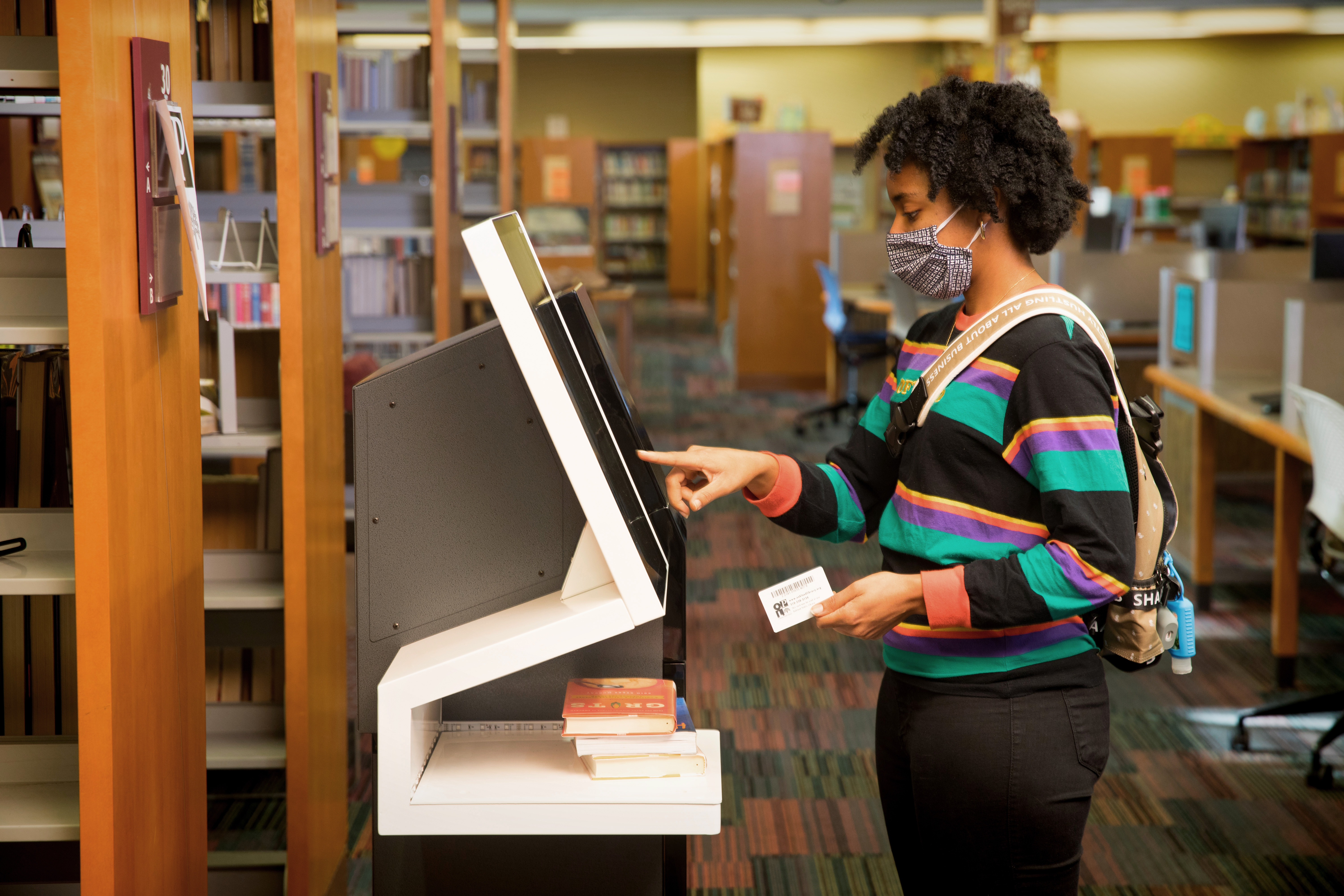 A woman in a colored striped shirt uses a self-check machine.
