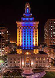 Photo of City Hall at night with blue light cast upon the building.