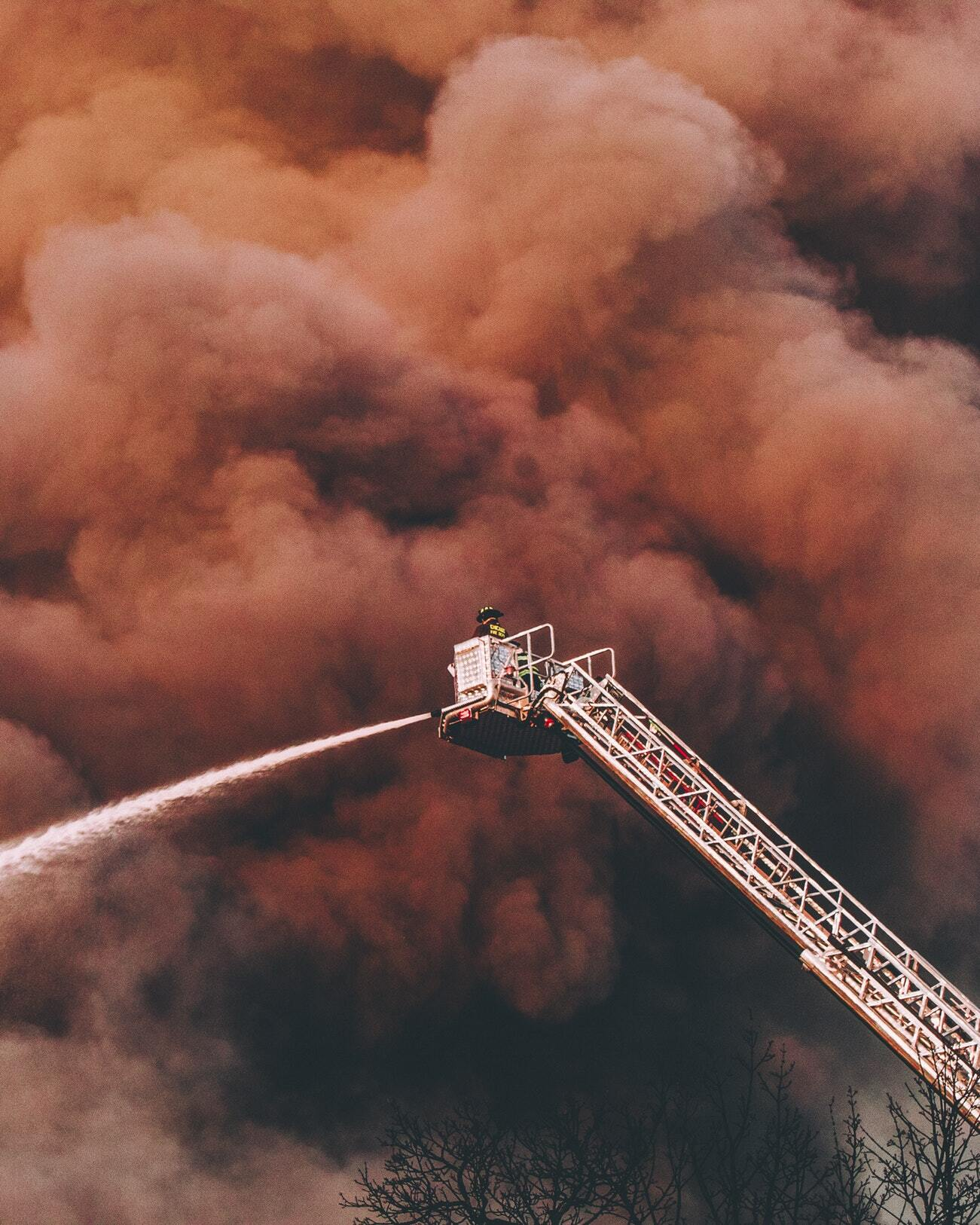 Photo of a fire department's crane spraying water against a backdrop of smoke from a raging fire