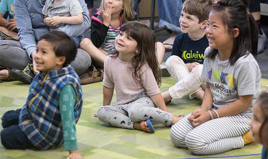 Young children sitting on a carpet during a magic show at OPL.