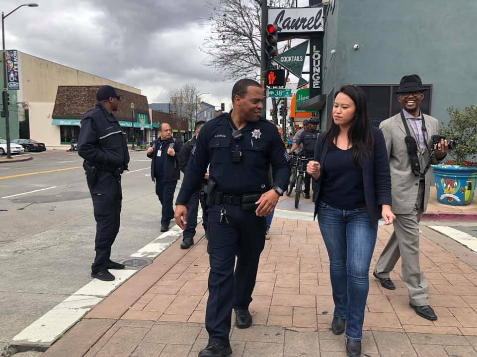 Councilmember Sheng Thao walks with a member of the Oakland Police Department along 38th Street in Oakland, CA. They stand on the sidewalk in front of the Laurel Cocktail Lounge.