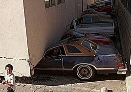 "An example of a building with an open, ground floor (""soft story""), which collapsed onto a row of parked cars during an earthquake."