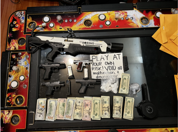 Photo of flame thrower, loaded firearms, cash, and narcotics.