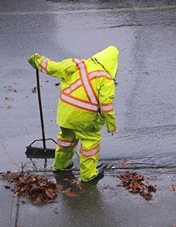 Photo of a person cleaning a storm drain in the rain