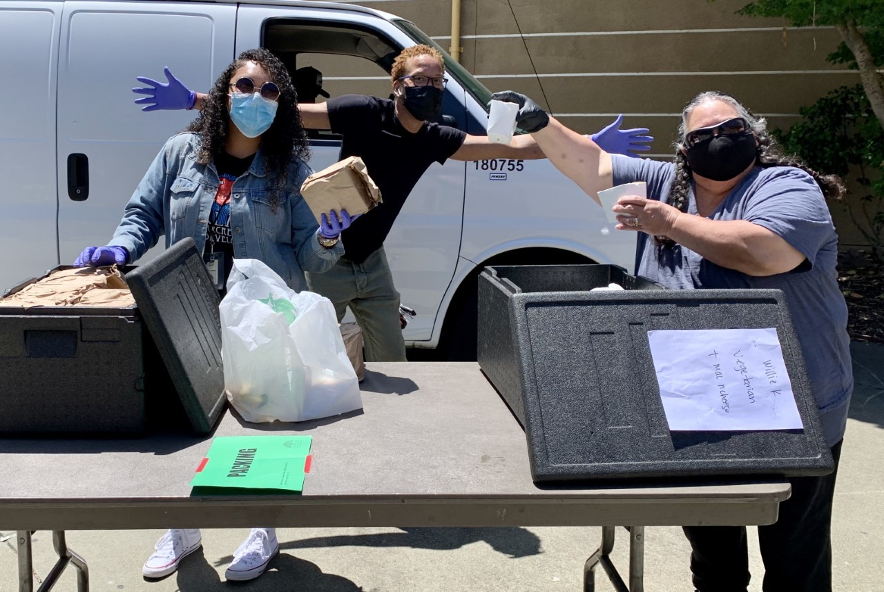 Three people display meals provided by the Summer Lunch Program.
